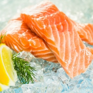 Fresh salmon on a bed of ice and a lemon slice