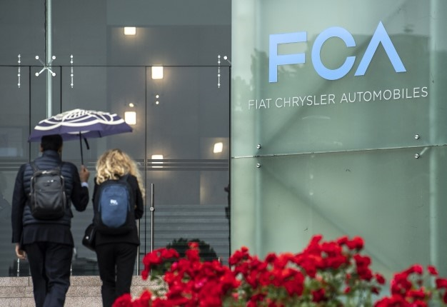 In this file photo taken on May 27, 2019 people walk past the logo of Fiat Chrysler Automobiles (FCA) at the Fiat Mirafiori car plant in Turin, northern Italy. Fiat Chrysler, Peugeot discuss merger to create $50bn entity. MARCO BERTORELLO / AFP
