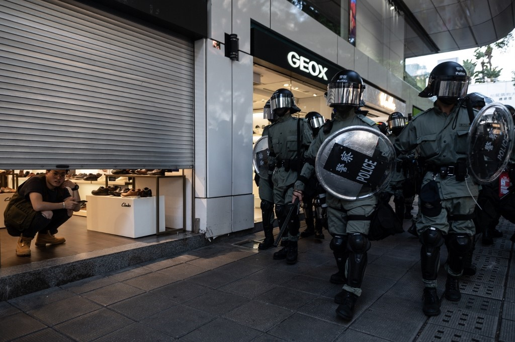 Police march past as a store employee looks out from a partially-closed shutters as pro-democracy protesters gather for a singing rally in Tsim Sha Tsui district in Hong Kong on November 2, 2019.