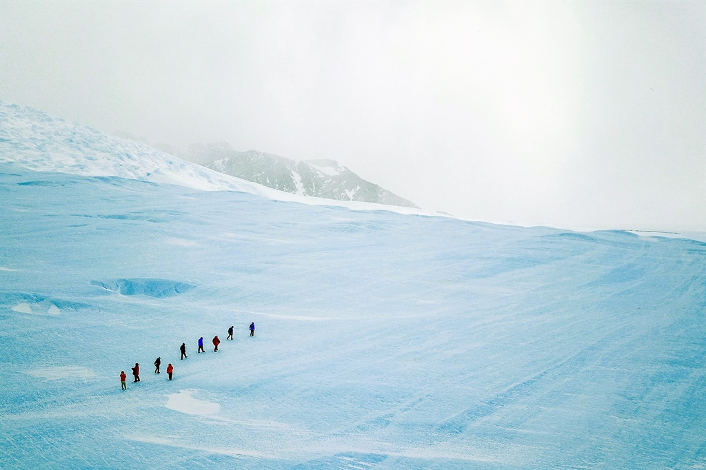 A group of guests hike up blue-ice during an excur
