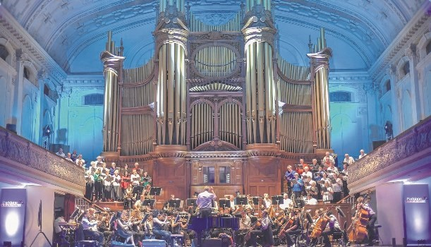 The KZN Philharmonic Orchestra and Pietermaritzburg Proms Choir conducted by Richard Cock in front of the pipe organ in the Pietermaritzburg City Hall.