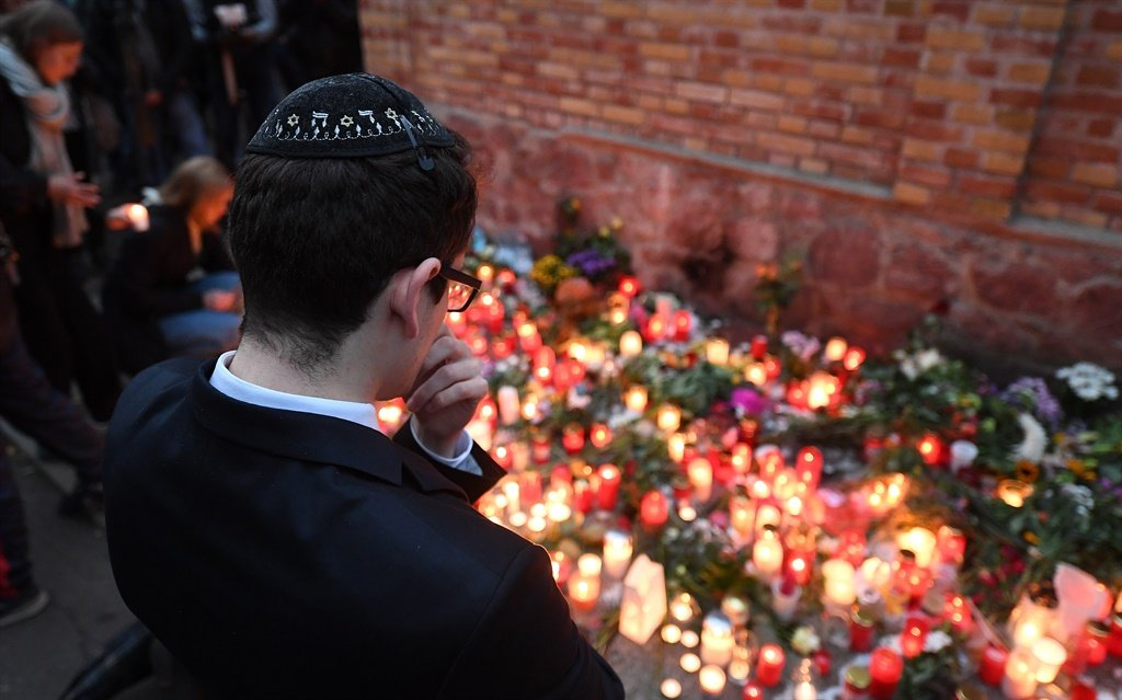 A young man with Kippa stands in front of candles