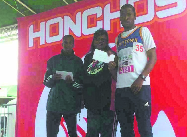 photo: supplied Umvoti Athletic Club members Thulani Zondi (left) and Zama Dlamini (right) receive gifts from the chairperson of the Save Orion Athletic Club.