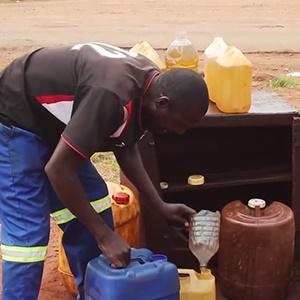 A roadside fuel helps a customer outside Harare, Z