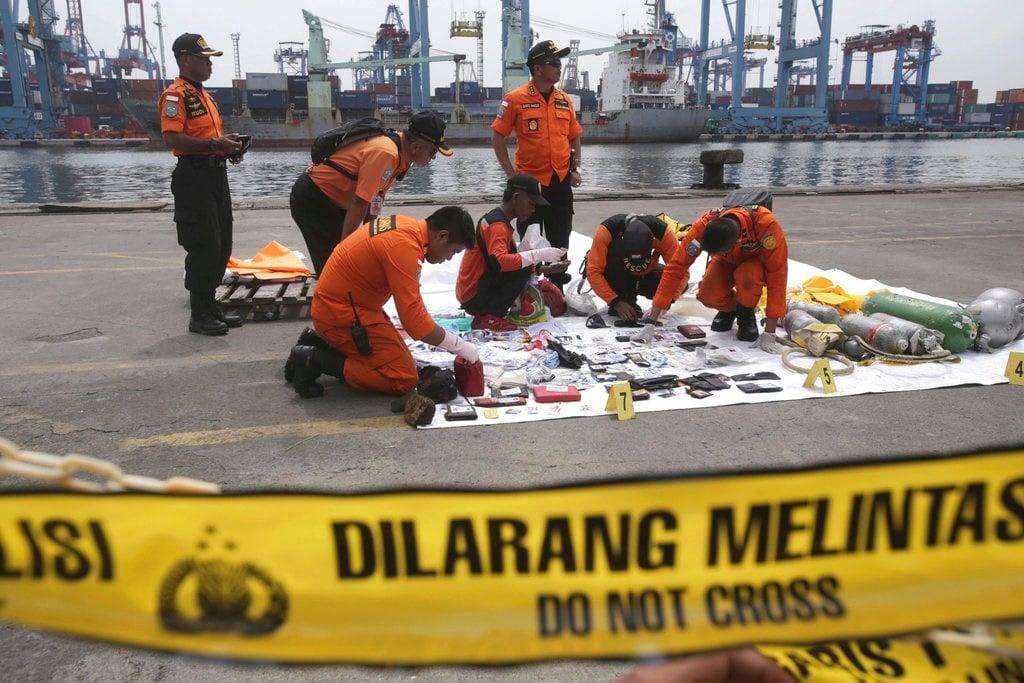 Rescuers examine personal belongings of passengers