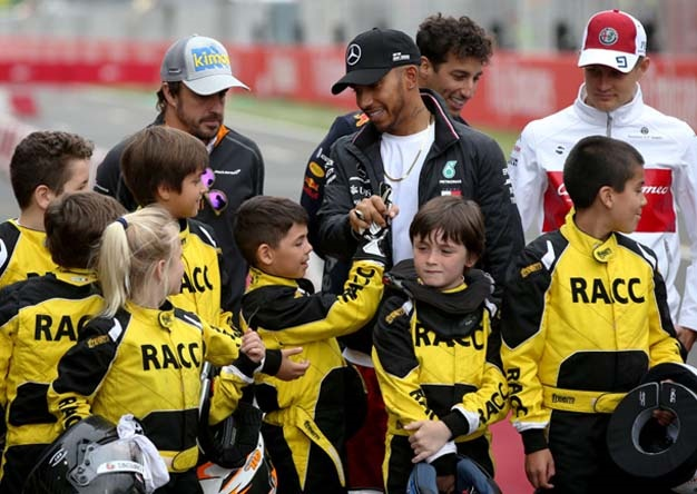 Lewis Hamilton of Great Britain and Mercedes GP shakes hands with karting kids during previews ahead of the Spanish Formula One Grand Prix at Circuit de Catalunya on May 10, 2018 in Montmelo, Spain.  (Photo by Charles Coates/Getty Images)
