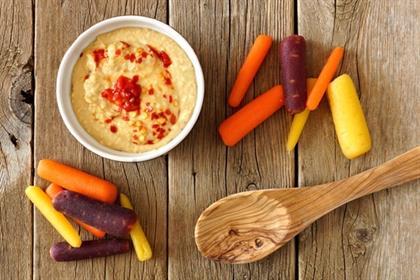 Baby rainbow carrots with hummus dip and spoon, ov
