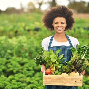 woman holding fruit and vegetables outdoors