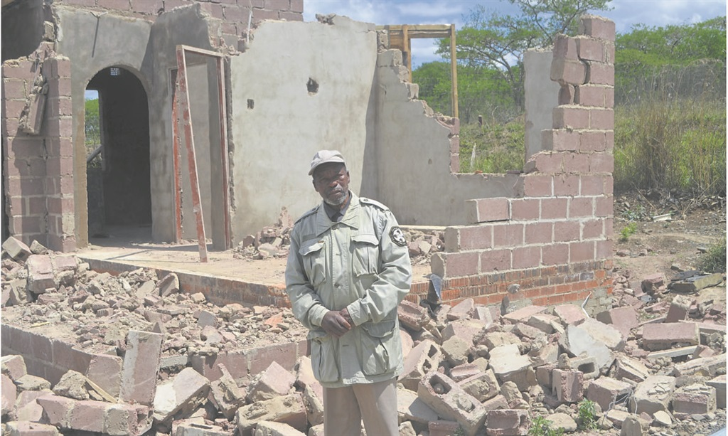 Shiya Zuma, brother to Mbothweni Zuma who was shot by Msunduzi guards during a demolition in the area, stands in front of one of the destroyed houses.