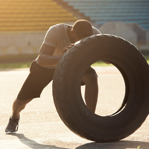 man using tyre to exercise with
