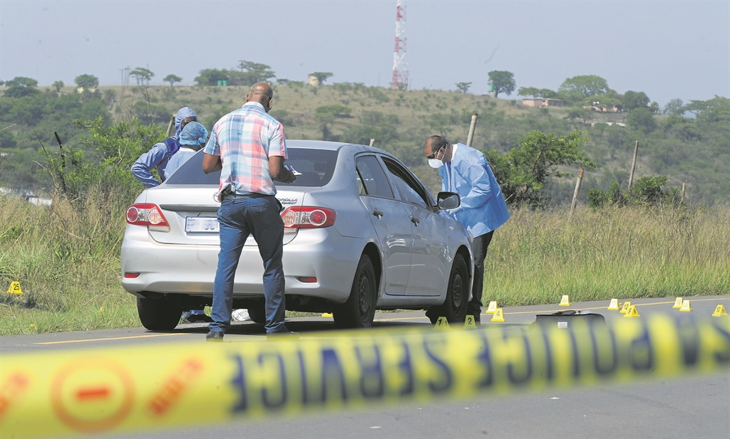 Police forensics staff inspect a crime scene where a man was shot dead on Monday morning on the R33 near Albert Falls. The yellow markers indicate where bullet casings were found.