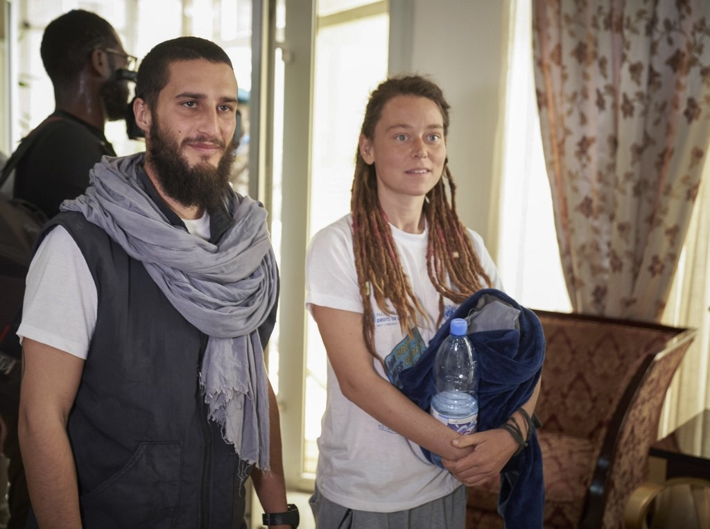 Italian Luca Tacchetto (L) and Canadian Edith Blais (R) are greeted by officials as they arrive at the airport in Bamako on March 14, 2020, after their release by UN peacekeepers. (AFP)