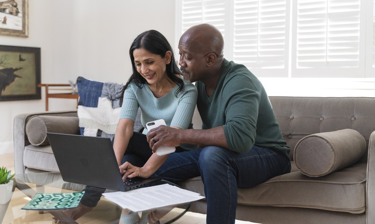 Couple sitting together on a couch and using a PC