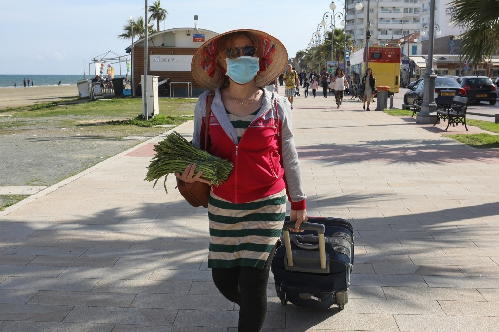 masked woman walking with asparagus and suitcase