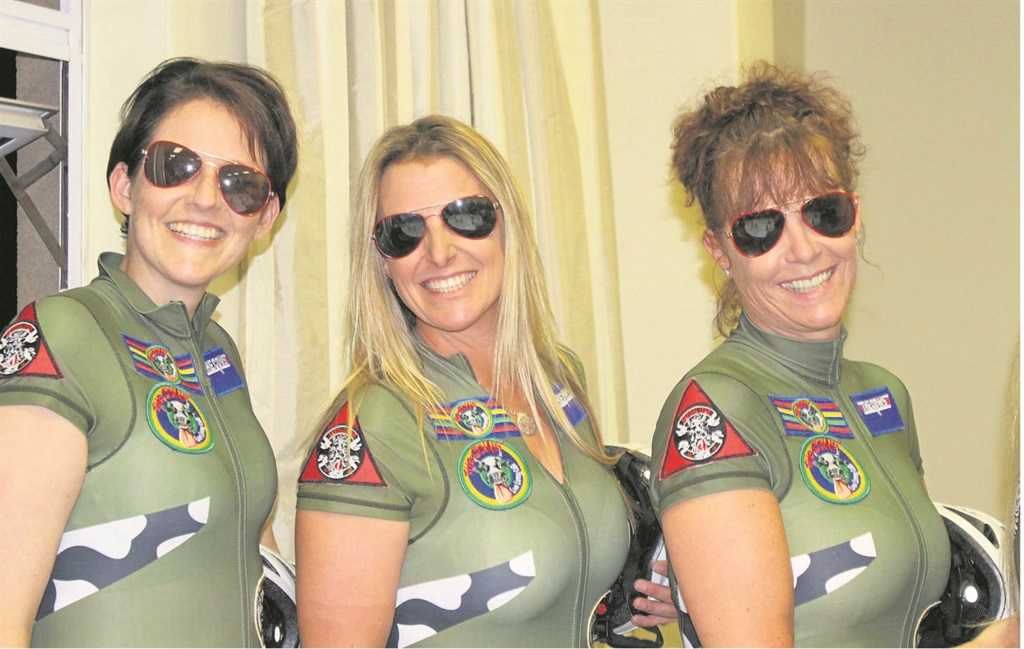 PHOTO: SUPPLIEDShowing off their Apocalypse Cows flights suits for the Telkom 947 Cycle Challenge are (from left) Delyse van Breda, Kim Heger, and Iris Varty.