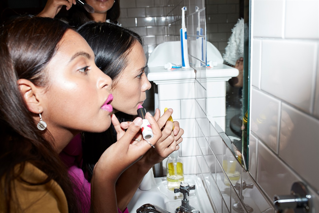 Young friends doing make-up together while looking