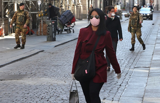 A woman wearing protective mask walks as military soldiers are patrolling in downtown after the Government Decree declaring all of Italy a protected area. (Getty Images)