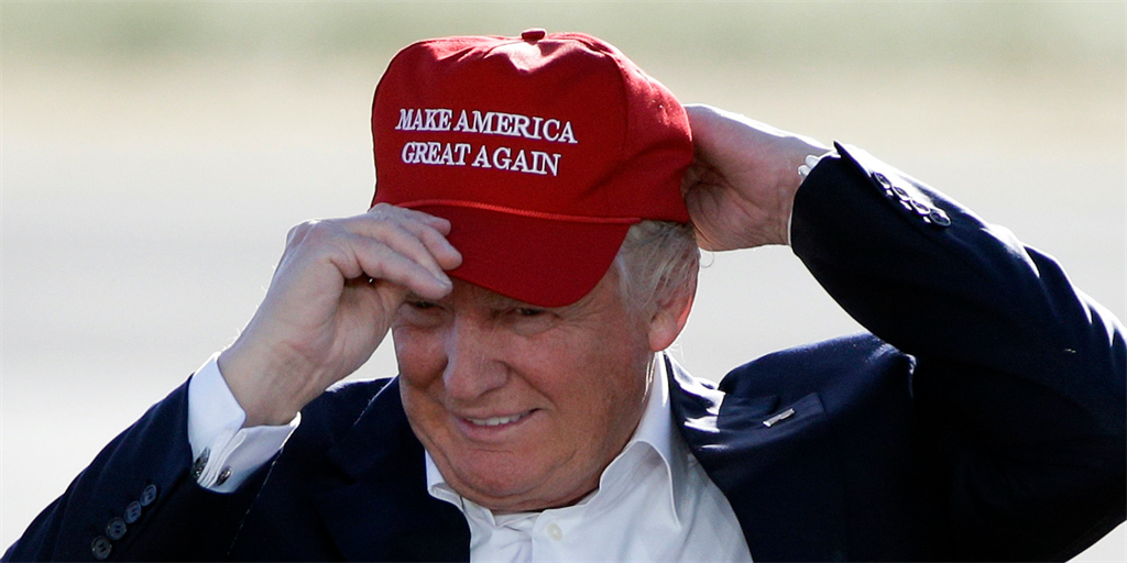 """President Donald Trump dons a red """"Make America Great Again"""" hat"""