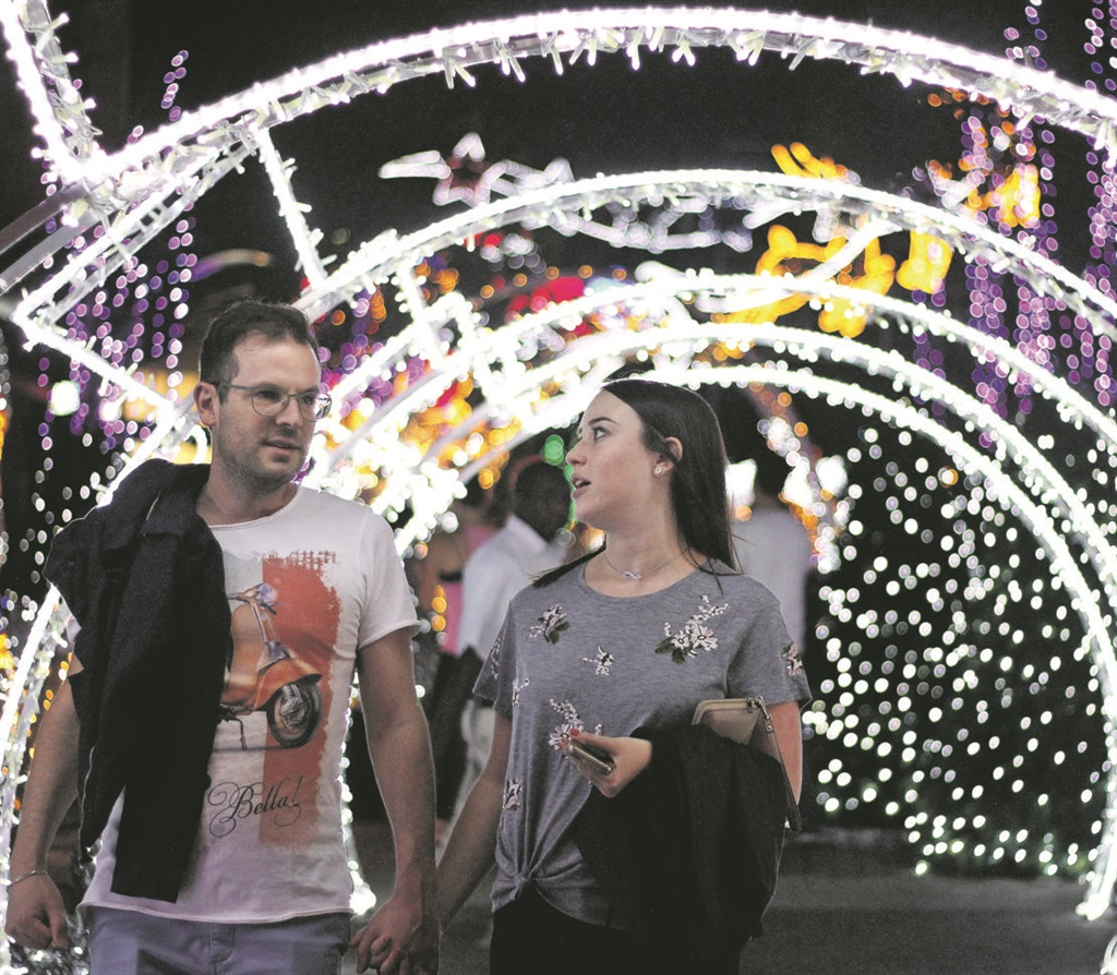A TIME TO DECOMPRESS A couple at the Melrose Arch Precinct in Johannesburg. Melrose Arch holds a Christmas lights campaign each year, showcasing bright lights and an exciting festive entertainment programme for the whole family. Picture: Rosetta Msimango