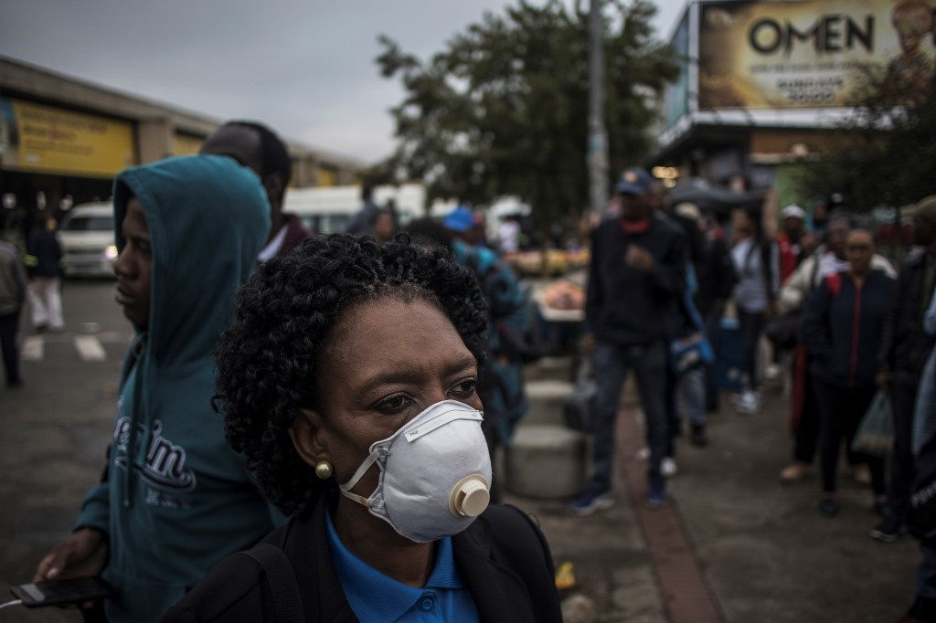 A commuter wearing a mask as a preventive measure against the COVID-19 coronavirus queues at the Bara taxi rank in Johannesburg.