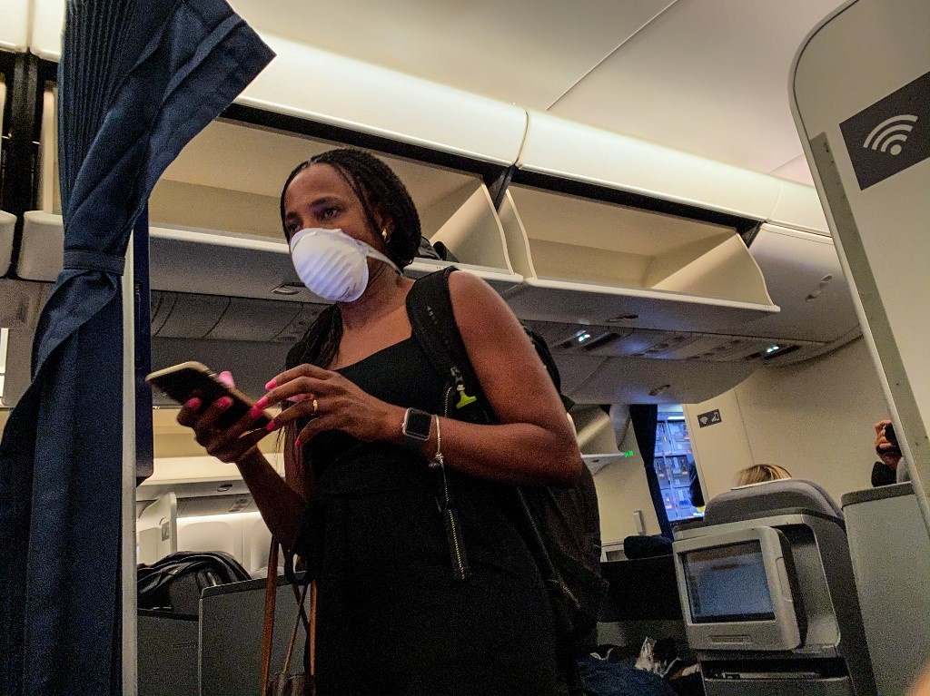 Passengers wear face masks as a preventive measure while they talk to a security guard at the OR Tambo International Airport in Johannesburg. (Guillem SARTORIO / AFP)
