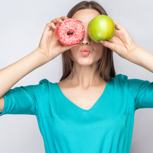 woman holding donut and apple