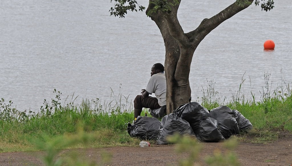 A man sits next to piles of rubbish on the banks of the Duzi at Camps Drift yesterday.Photo.Ian CarbuttPHOTO:
