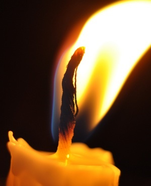 The candle with flame in dark background