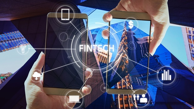 """Fintech"" word on digital virtual screen with two businessman hands holding smartphones background."