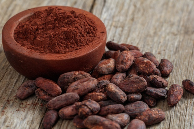 Cocoa beans and powder on a wooden surface
