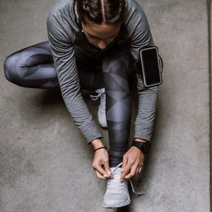 woman lacing up running shoes