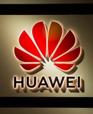 A logo sits illuminated outside the Huawei booth o