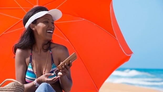 Happy woman with sun visor applying sunscreen, sit