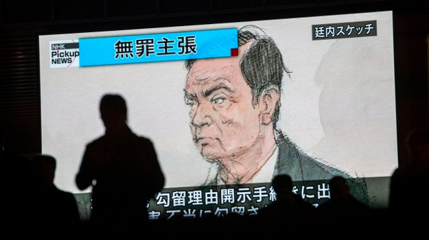 Pedestrians pass by a screen showing a news program displaying a sketch of former Nissan chief Carlos Ghosn in the courtroom, in Tokyo on January 8, 2019.