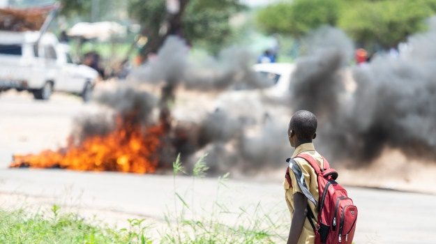 A school boy looks at a burning barricade during