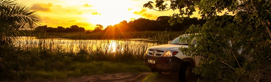 African sunset on lake behind 4x4