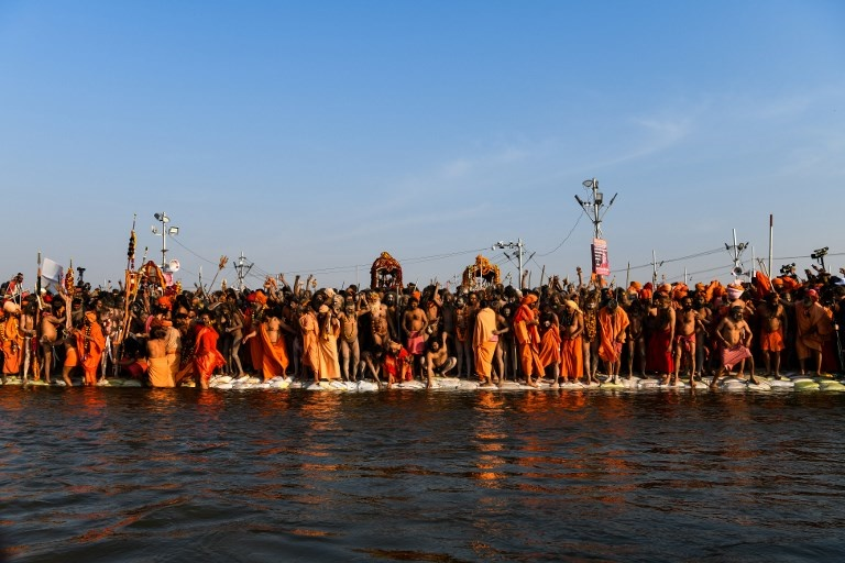 Indian sadhus (Hindu holy men) wait to jump into t