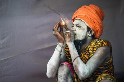 An Indian sadhu (Hindu holy man) smokes as he sits