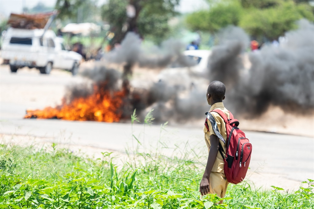 A school boy looks at a burning barricade during a