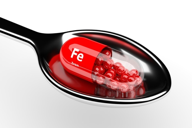 3d iron pill on spoon over white background
