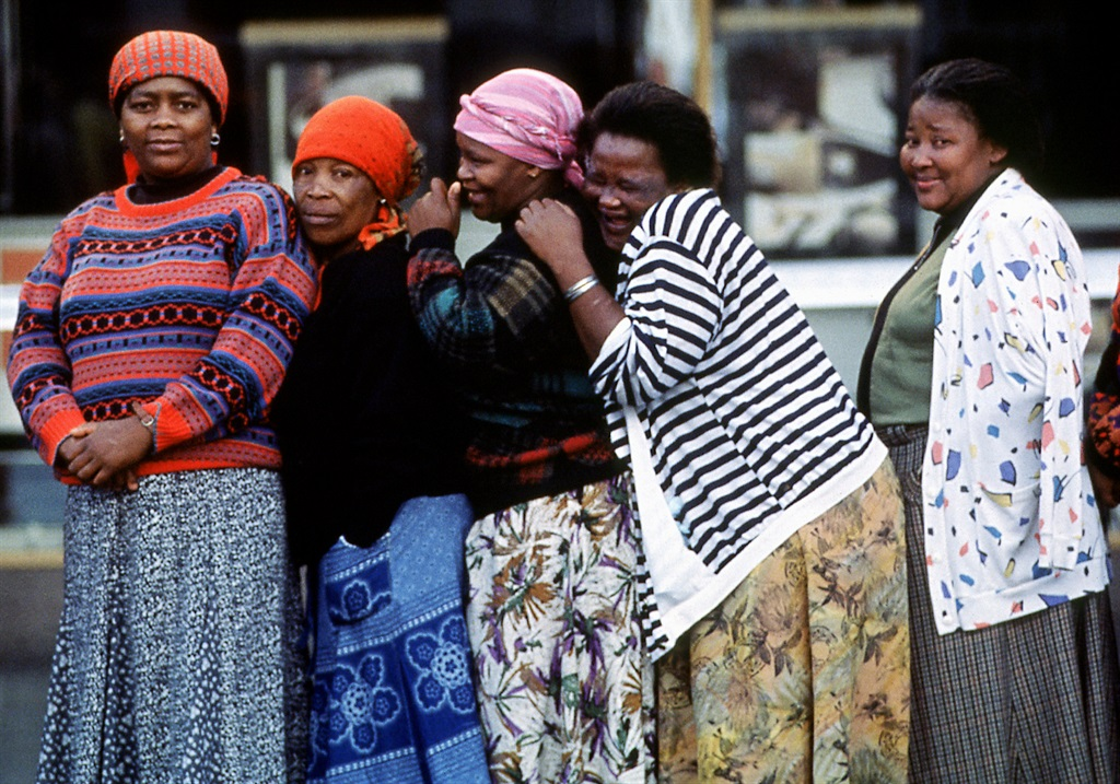 A group of women from Mdamstane Township giggle as they wait to vote in their countrys first democratic election, in East London, South Africa, 1994. (Photo by Susan Winters Cook/Getty Images)