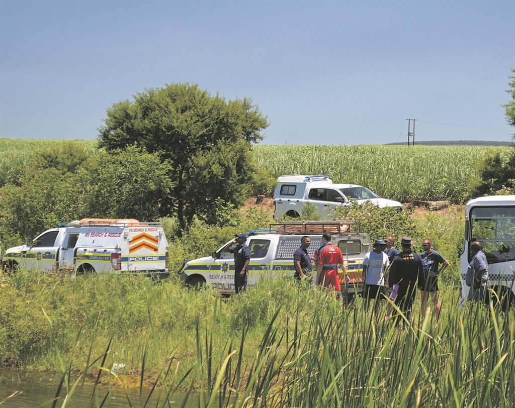 Police gather near the dam after the body of 16-year-old Mthobisi Mnguni, who drowned while swimming with friends at a Camperdown farm dam on Friday afternoon, was recovered on Monday.