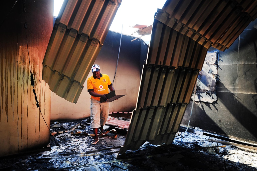 In 2013, Thulamela agricultural municipality manager Sammy Minga was left to salvage what he could at the department of agricultural office in Malamulele. The office was set alight by protesters during a demarcation protests in the area in Malamulela, Limpopo. Residents barricaded roads, looted stores and burned most government buildings during the protest. The community wanted their own municipality. Picture: Leon Sadiki/City Press