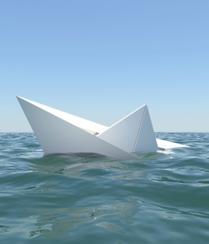 White paper boat is sinking in the sea water. The