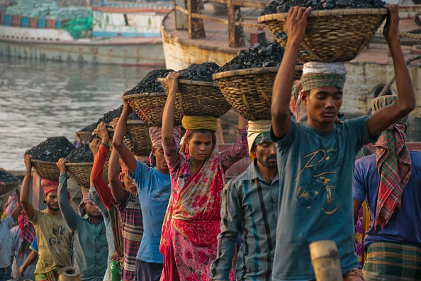 Workers are working in a domestic port in Dhaka, B