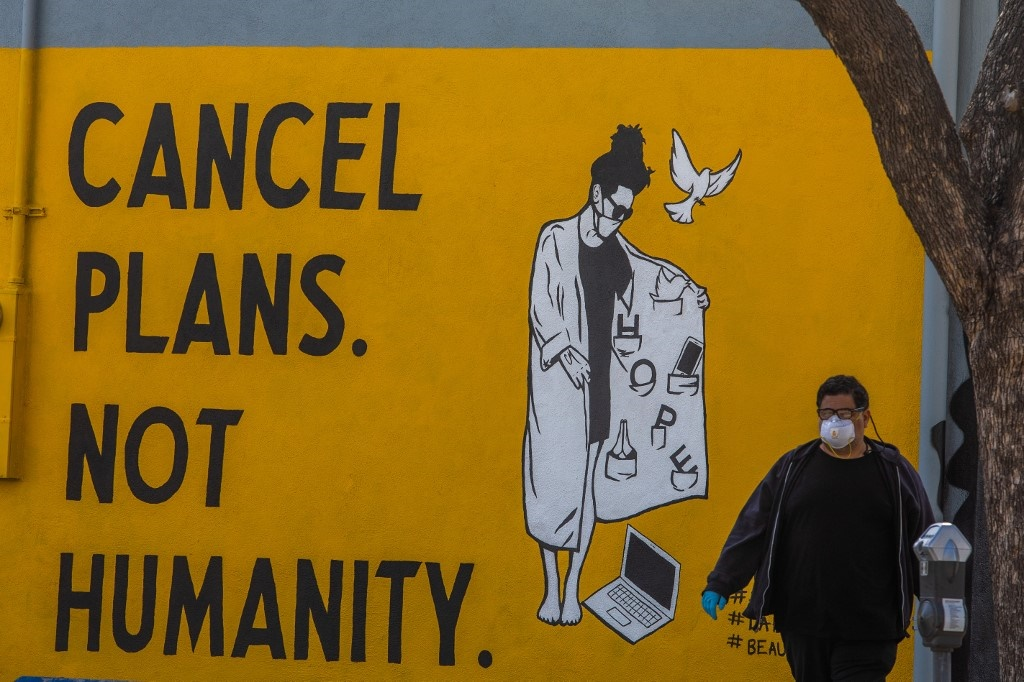 """A man wearing gloves and a face mask walks by a mural reading """"Cancel Plans Not Humanity"""" during the coronavirus (Covid-19) pandemic on April 4, 2020 in Los Angeles, California."""