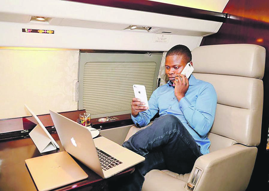 HIGH FLIER Self-styled prophet Shepherd Bushiri uses his hi-tech gadgetry while sitting in the Gulfstream private jet that his wife allegedly paid for in cash