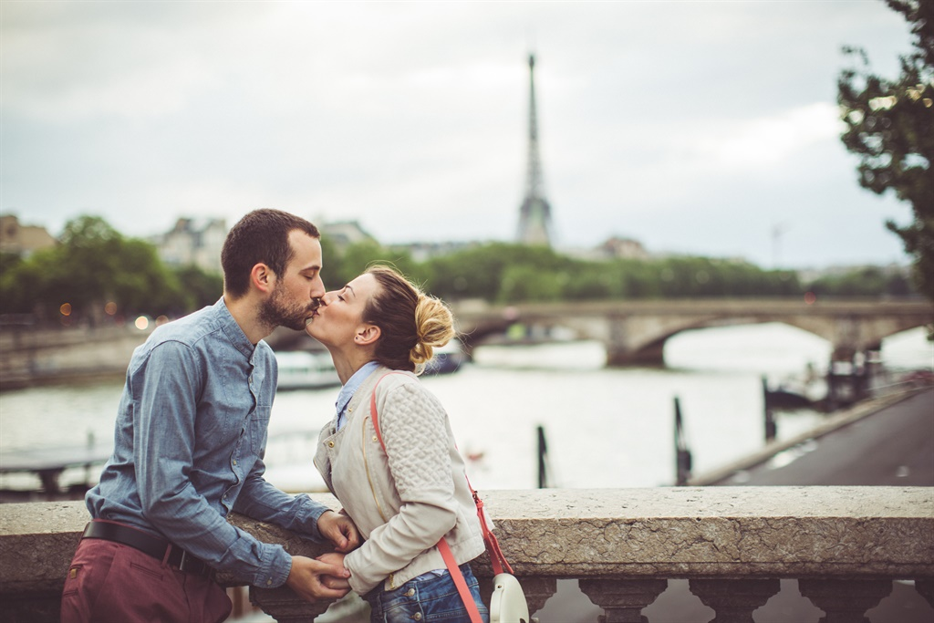 Young loving couple is kissing in Paris, France, o