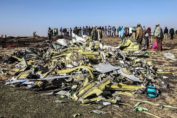 TOPSHOT - People stand near collected debris at th