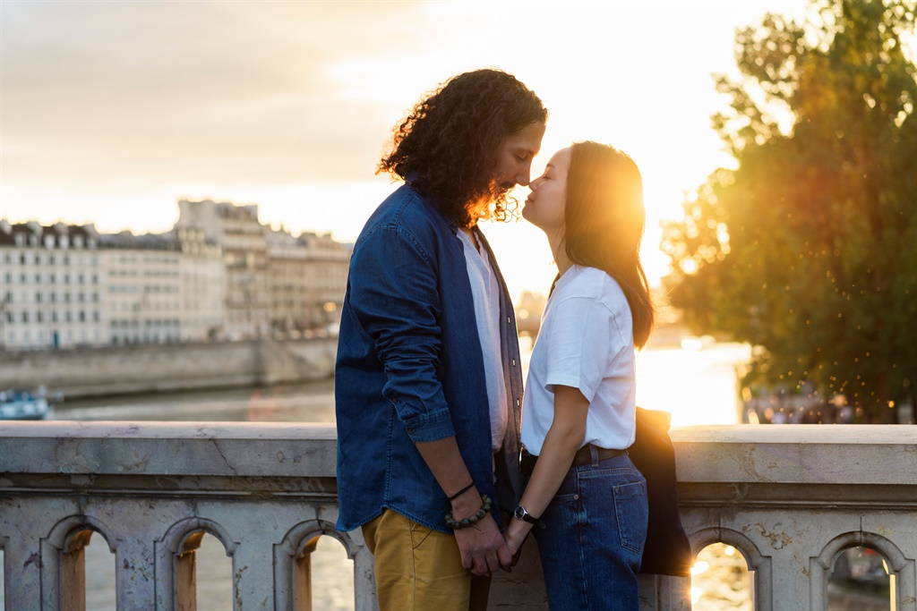 A couple kissing on a bridge over the Seine river in Paris. (Photo: Getty Images)